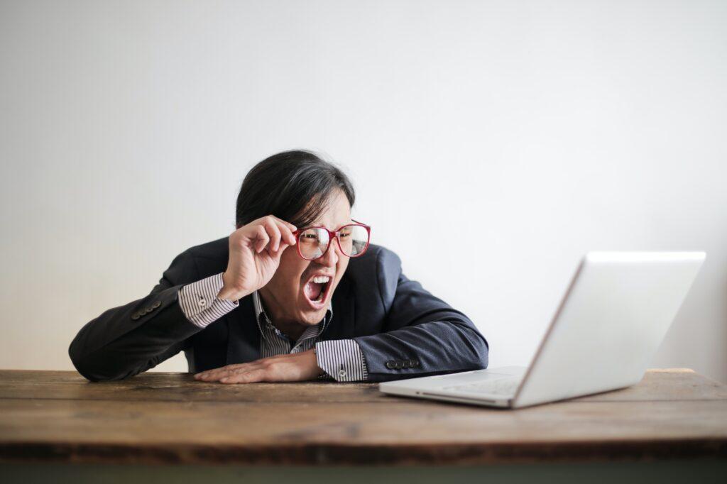 Immagine di un uomo che fatica a leggere dal computer