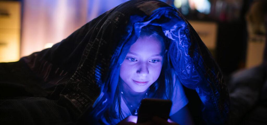 Bambina che guarda luce blu sul celluare